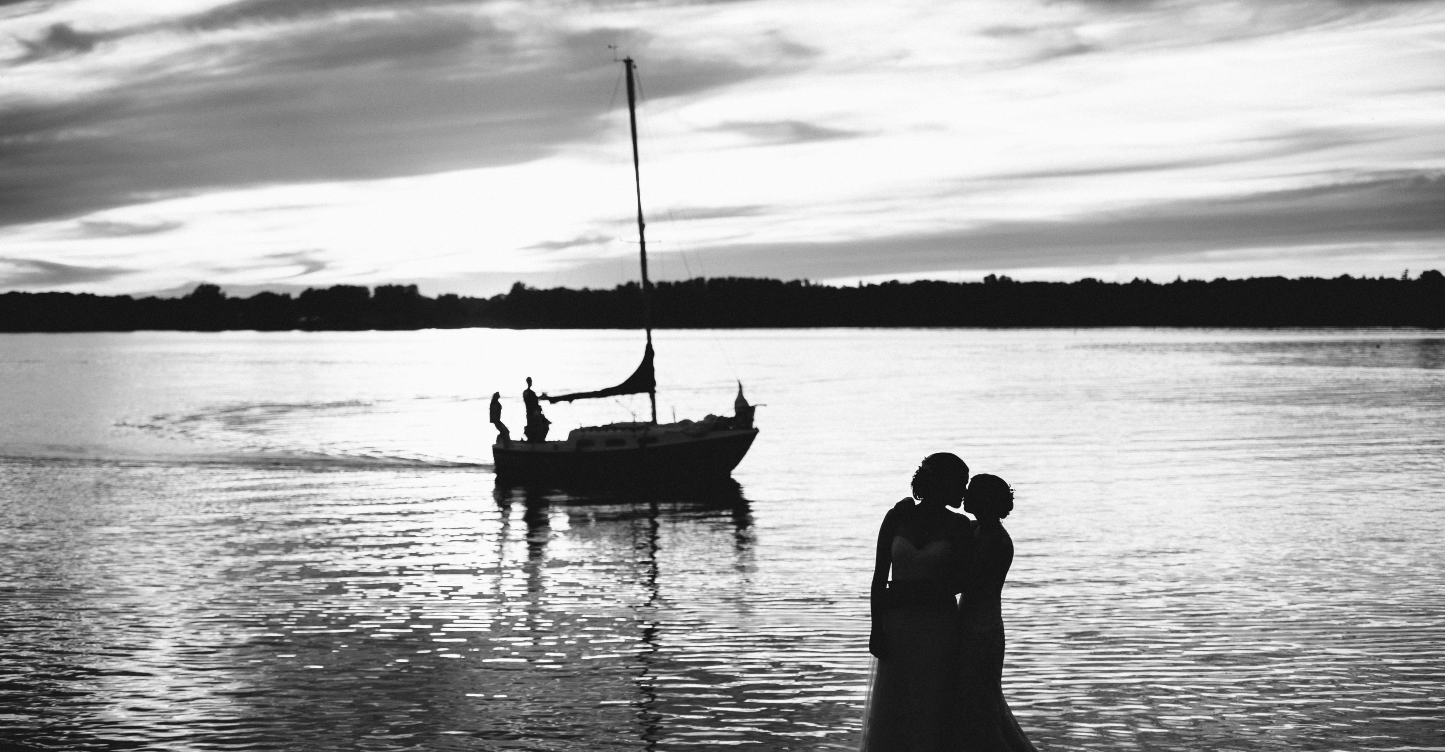Two brides - same sex couple kiss in a silhouette black and white picture taken with the Ottawa river in the background