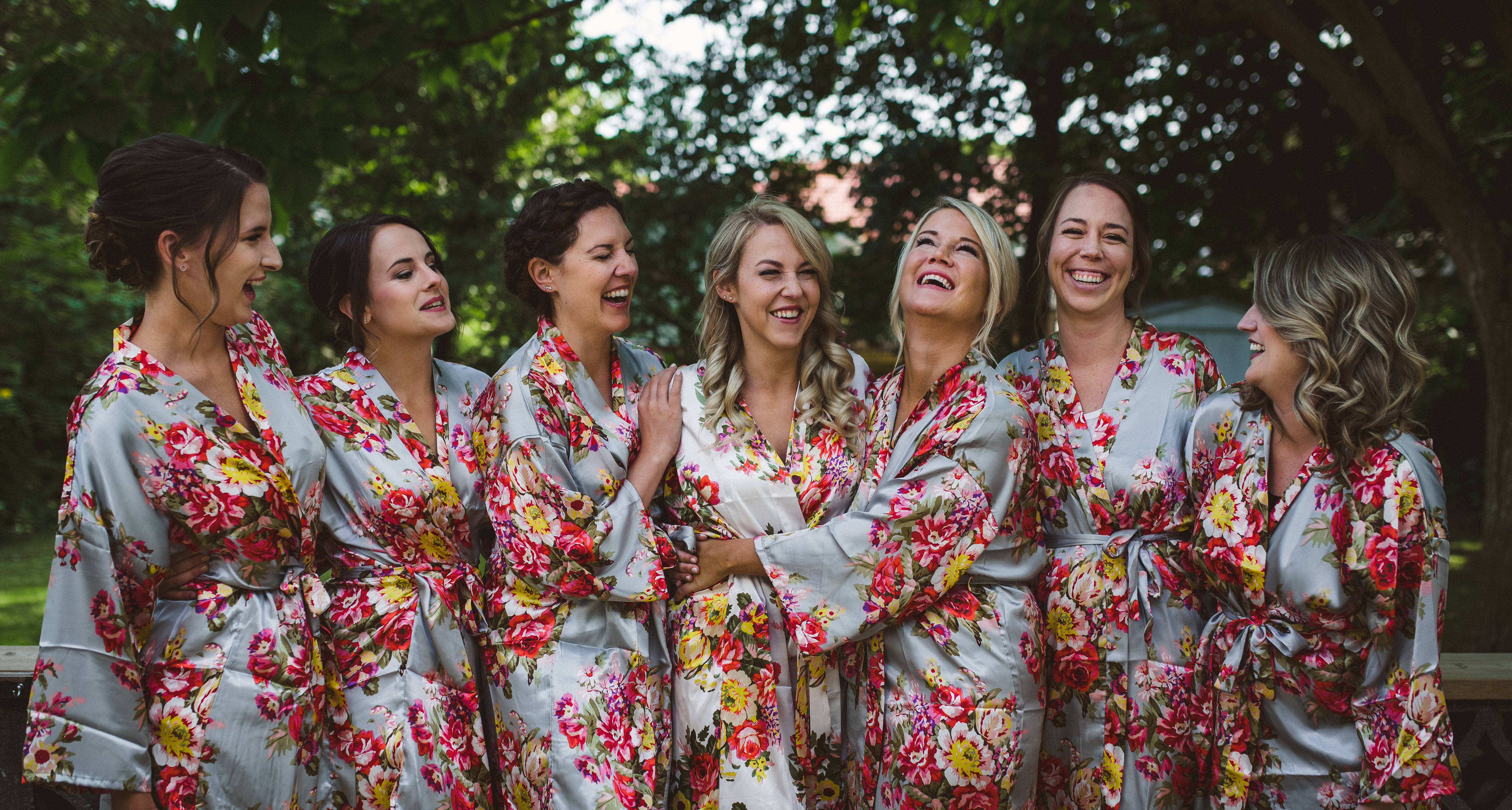 Bride and bridesmaids huddle in pretty matching floral robes for a group photo before getting ready for the wedding day