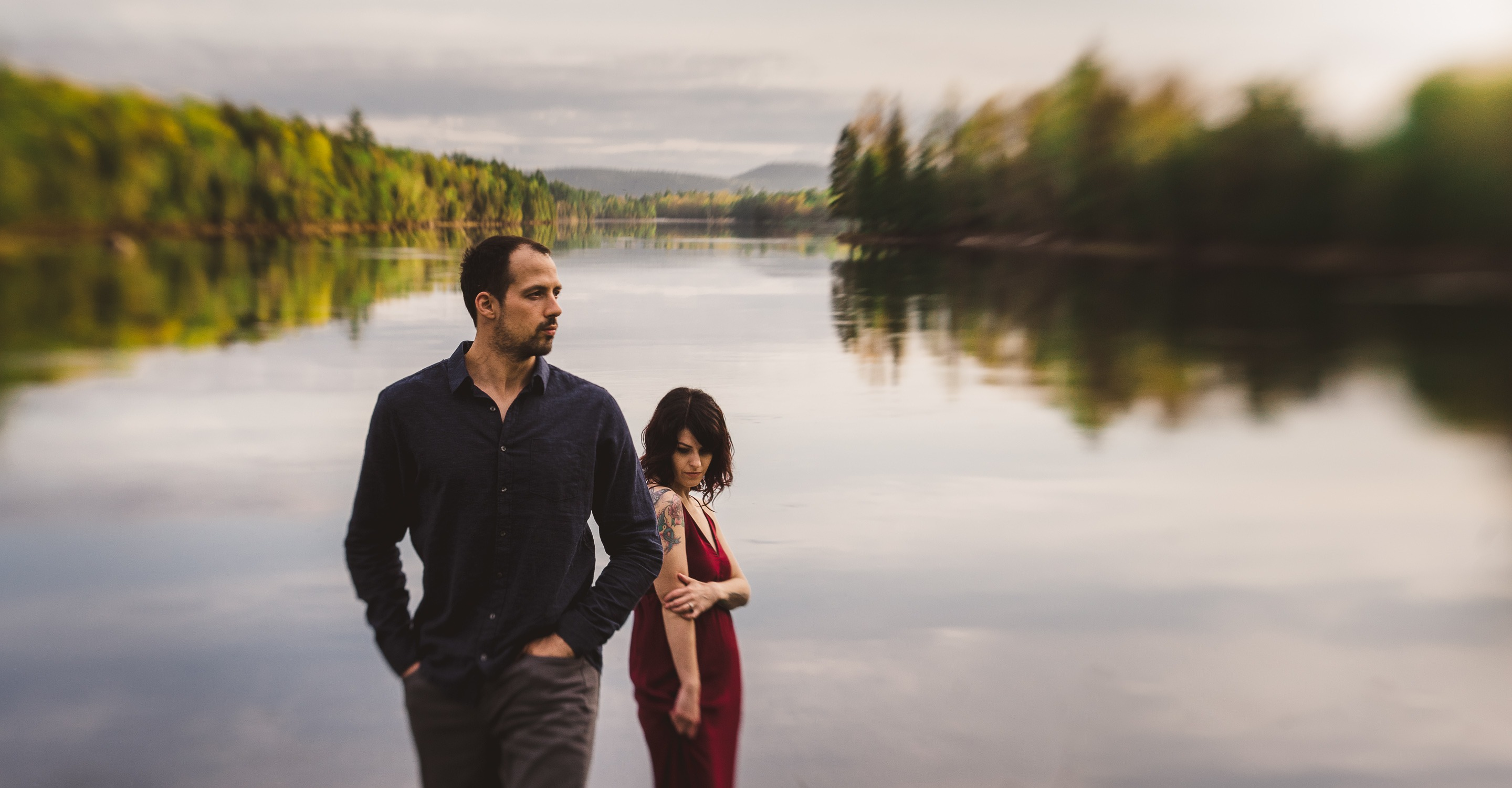 Couple pose in front of a river for their engagement session
